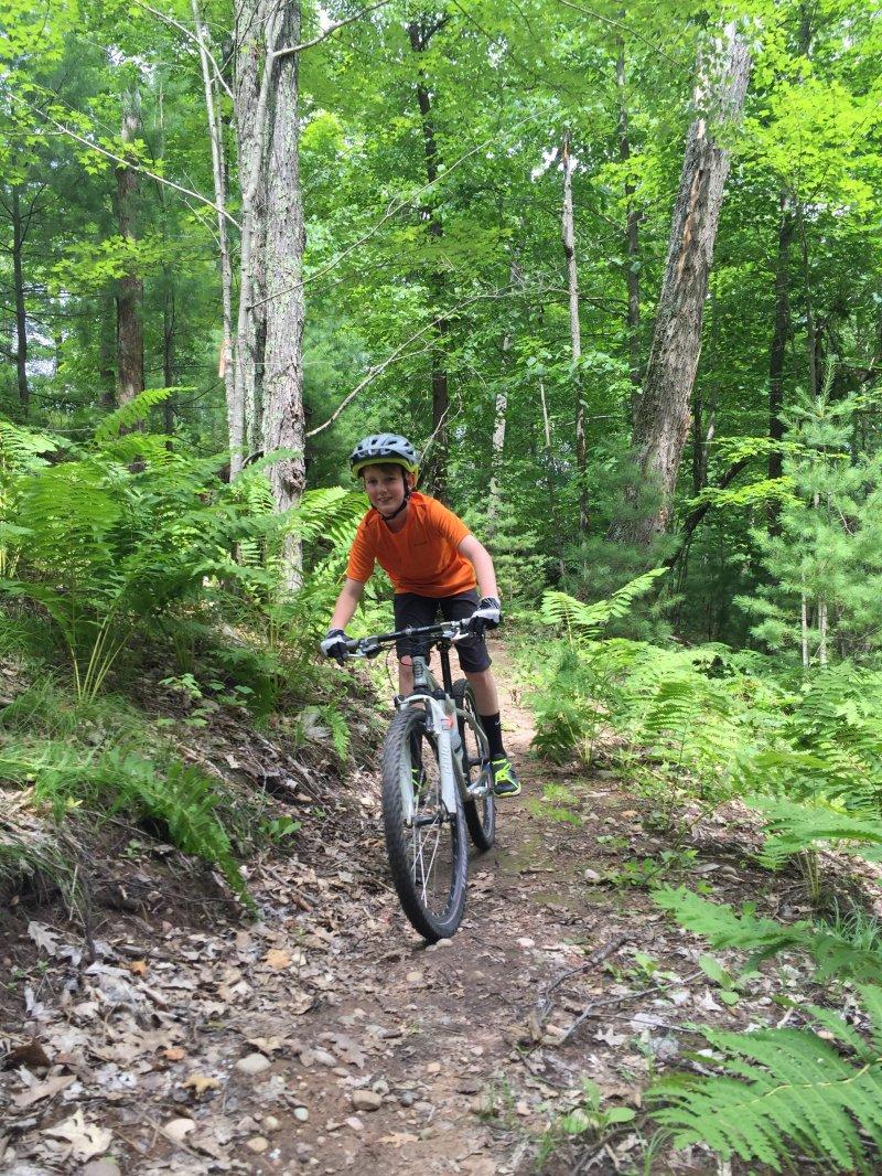 Boy biking Northwoods Zip Line Trail